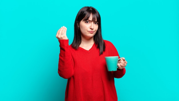 Mooie vrouw met grote maten die een capice of geldgebaar maakt en je zegt dat je je schulden moet betalen!