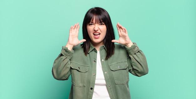 Mooie vrouw met grote maten schreeuwend van paniek of woede, geschokt, doodsbang of woedend, met de handen naast het hoofd