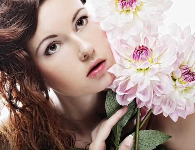 Mooie vrouw met grote roze bloemen