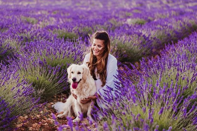 Mooie vrouw met haar golden retrieverhond op lavendelgebieden bij zonsondergang.