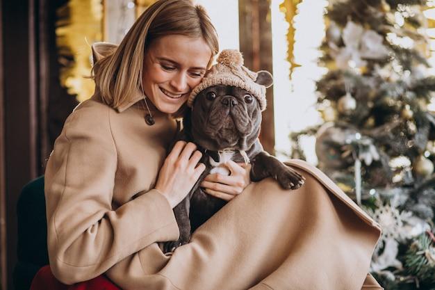 Mooie vrouw met haar schattige franse bulldog in warme outfit