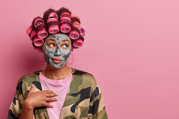 Mooie vrouw met haarkrulspelden past kleimasker toe, kijkt opzij met doordachte uitdrukking, gebruikt cosmetisch product, draagt kaki badjas, geïsoleerd op roze muur lege ruimte