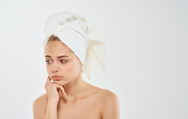 Mooie vrouw met handdoek op hoofd blote schouders licht bebouwd uitzicht