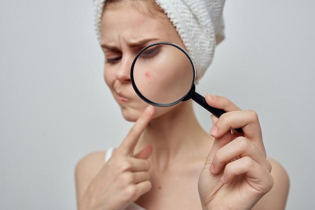 Mooie vrouw met handdoek op hoofd huidverzorging vergrootglas in de buurt van gezicht