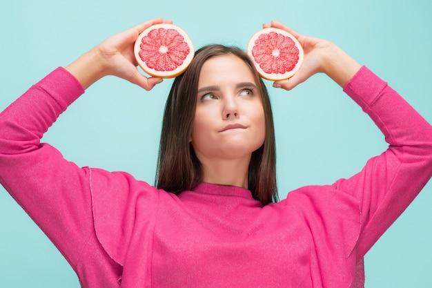 Mooie vrouw met heerlijke grapefruit in haar armen