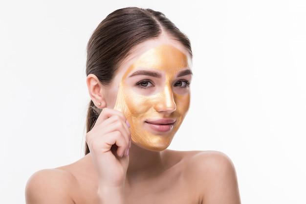 Mooie vrouw met het gouden gezicht van de huid kosmetische aanraking dat op witte muur wordt geïsoleerd. schoonheid huidverzorging en behandeling