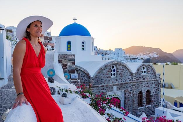 Mooie vrouw met hoed in oia, santorini, griekenland