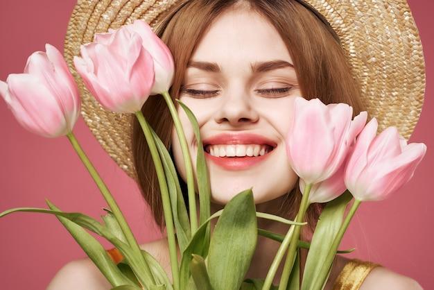 Mooie vrouw met hoed roze bloemen boeket glamour close-up