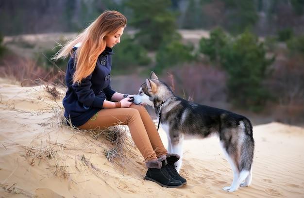 Mooie vrouw met jonge hond malamute zit op het zand. vriendschap tussen mens en hond