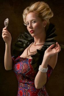 Mooie vrouw met juwelen en een spiegel die aan u kijkt