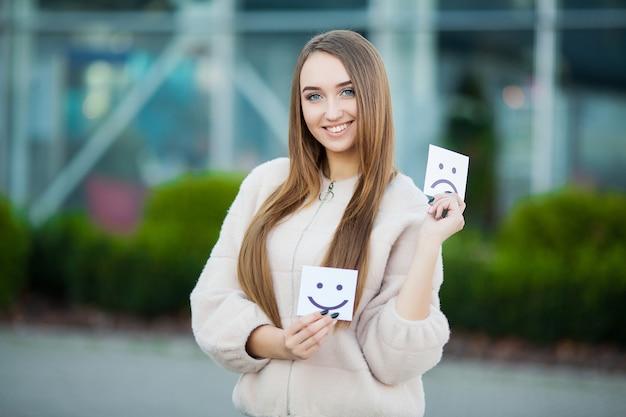 Mooie vrouw met kaarten met droevige en grappige glimlach
