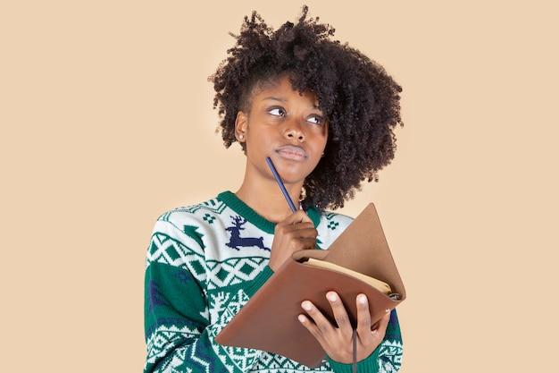 Mooie vrouw met kerstkleren een notitieboekje en een potlood, brief voor cadeaus
