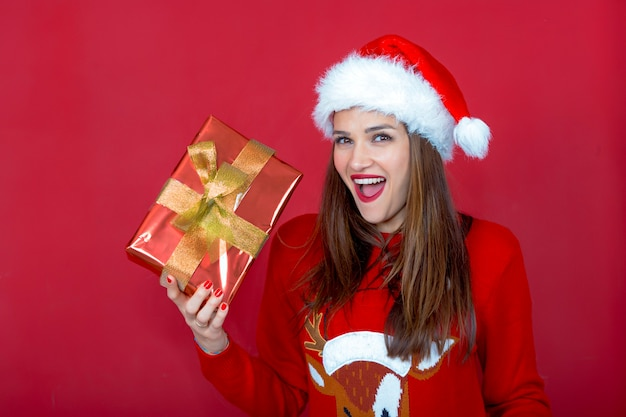 Mooie vrouw met kerstmis met kerstman hoed en vrolijke sympathieke uitdrukking die in haar hand een pakket laat zien verpakt in glanzend inpakpapier en strik