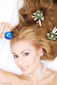 Mooie vrouw met kerstmisbal en ornamenten