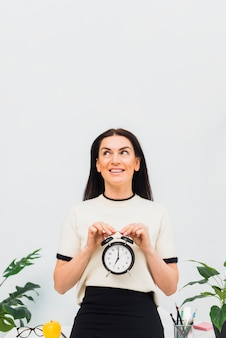 Mooie vrouw met klok in handen glimlachen