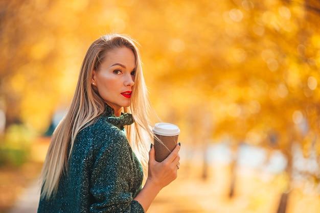 Mooie vrouw met koffie in herfst park onder bladeren vallen op warme dag