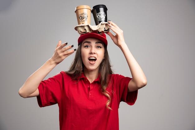 Mooie vrouw met koffiekopjes op haar hoofd.