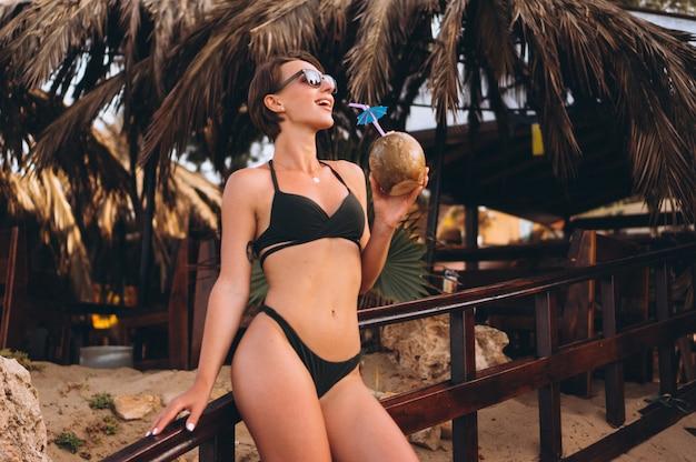 Mooie vrouw met kokos in bar