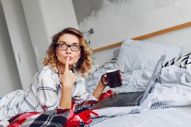 Mooie vrouw met kop koffie en laptop