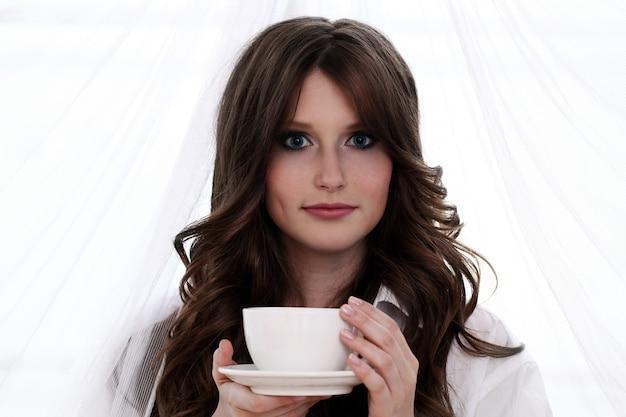 Mooie vrouw met kop warme koffie