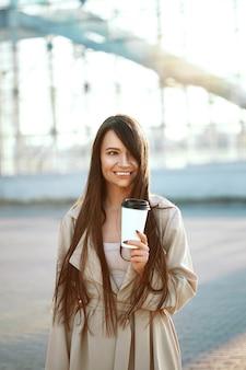 Mooie vrouw met kopje koffie lopen op straat. portret van aantrekkelijke jonge vrouw in stijlvolle kantoorkleren met kopje warme drank permanent buitenshuis