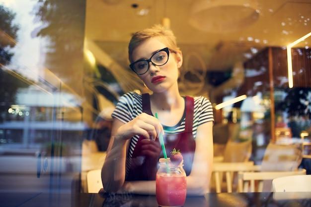 Mooie vrouw met kort haar in cafécocktailvakantie