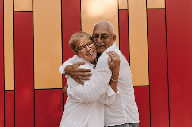 Mooie vrouw met kort haar in cool blouse knuffelen grijze harige man met snor in shirt met lange mouwen op rood en oranje.