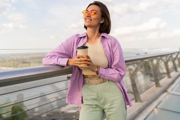 Mooie vrouw met kort kapsel lopen op moderne brug in winderige zomerdag