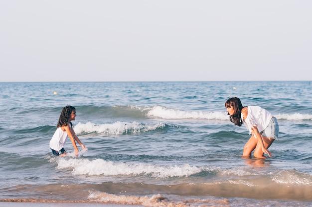Mooie vrouw met korte jeans en haar dochter die in het strandwater speelt