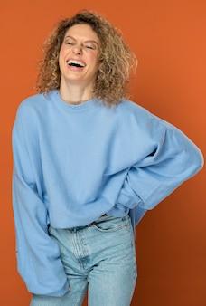 Mooie vrouw met krullend blond haar glimlachen