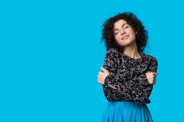 Mooie vrouw met krullend haar die zich op een blauwe muur omhelst met vrije ruimte die iets adverteert