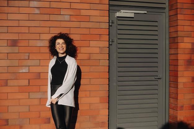 Mooie vrouw met krullend haar en bril poseren op een stenen muur terwijl ze vrolijk lacht