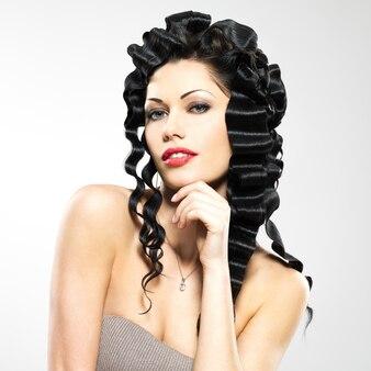 Mooie vrouw met krullend kapsel in fashoin-stijl vormt