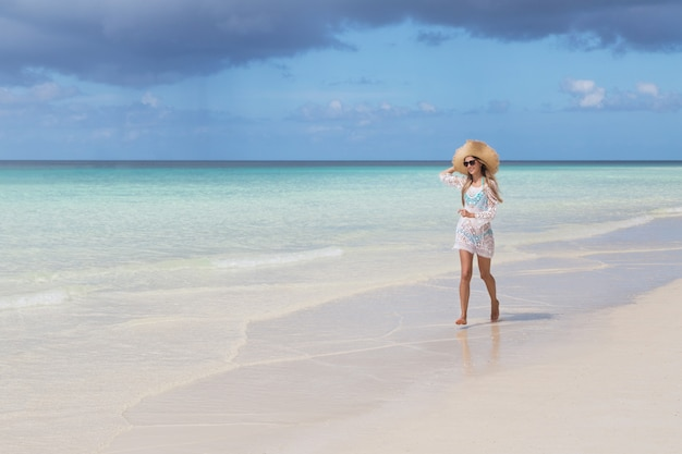 Mooie vrouw met lang blond haar in blauwe bikini die op tropisch strand met wit zand loopt