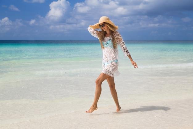 Mooie vrouw met lang blond haar in blauwe bikini ontspannen op tropisch strand met wit zand
