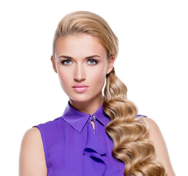 Mooie vrouw met lang blond krullend haar. portret van mannequin met lichte make-up. geïsoleerd op wit
