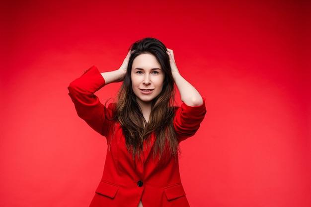 Mooie vrouw met lang donker steil haar in een rood kantoorpak, zwarte schoenen poseert voor de camera