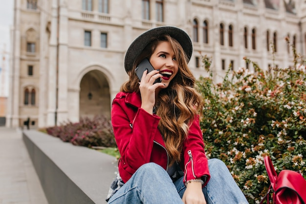 Mooie vrouw met lang golvend kapsel praten over telefoon op architectuurmuur