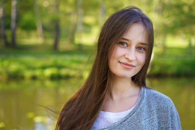 Mooie vrouw met lang haar dat zich naast het meer bevindt