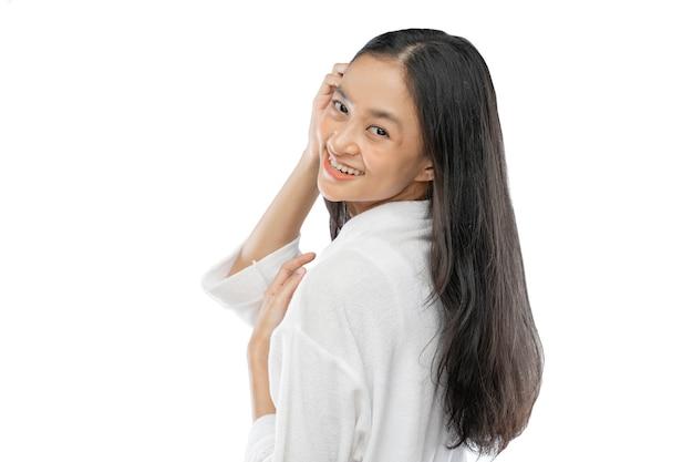 Mooie vrouw met lang haar dat zijwaarts over haar schouder naar de camera kijkt met een glimlach