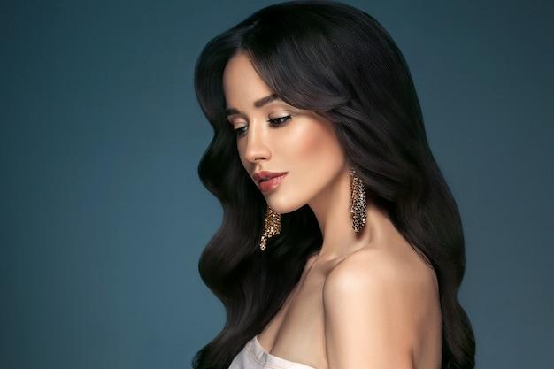 Mooie vrouw met lang haar, glans en krullend, schoonheid meisje vrouw over darl grijze achtergrond. studio opname.