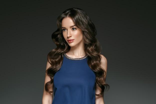 Mooie vrouw met lang haar, glans en krullend, schoonheidsmeisje. studio opname.