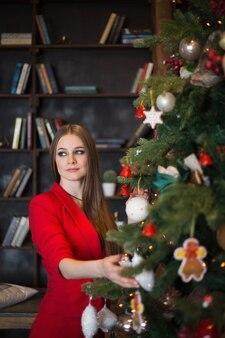 Mooie vrouw met lang haar in een rood pak in de buurt van een versierde boom en een open haard in een donker interieur