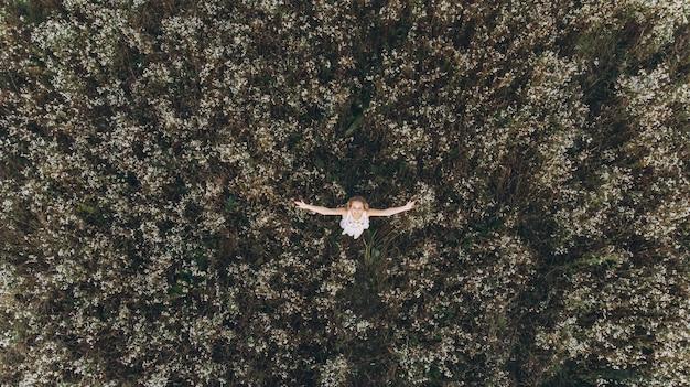 Mooie vrouw met lang haar in een witte jurk die zich in het veld met haar handen omhoog in de berg bevindt