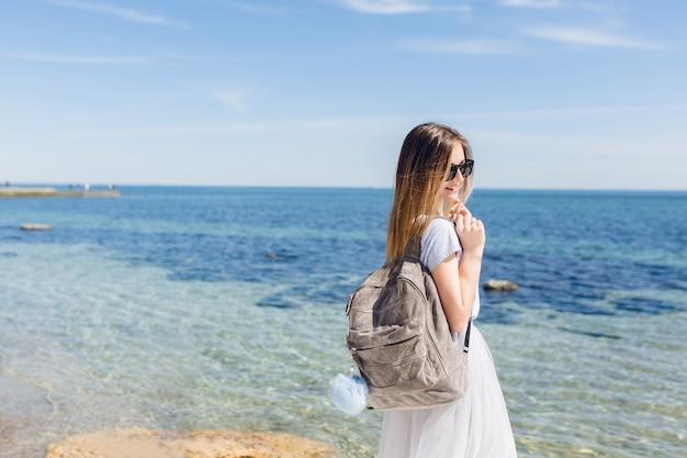 Mooie vrouw met lang haar loopt met tas in de buurt van zee