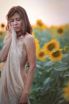 Mooie vrouw met lang haar sexy terug in een veld met zonnebloemen in de zomer in het zonlicht