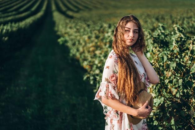 Mooie vrouw met lang krullend haar en sproetengezicht op besgebied. het meisje in een lichte kleding loopt in de zonnige zomerdag