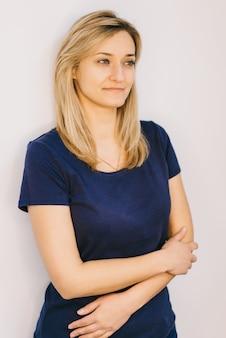 Mooie vrouw met lang recht blond haar op een witte muur.
