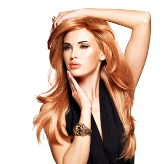 Mooie vrouw met lang recht rood haar in een zwarte jurk aan haar gezicht te raken. mannequin poseren. geïsoleerd op wit