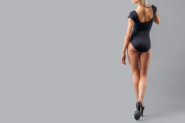 Mooie vrouw met lange benen op grijze achtergrond. sexy benen in zwarte schoenen met hoge hakken.